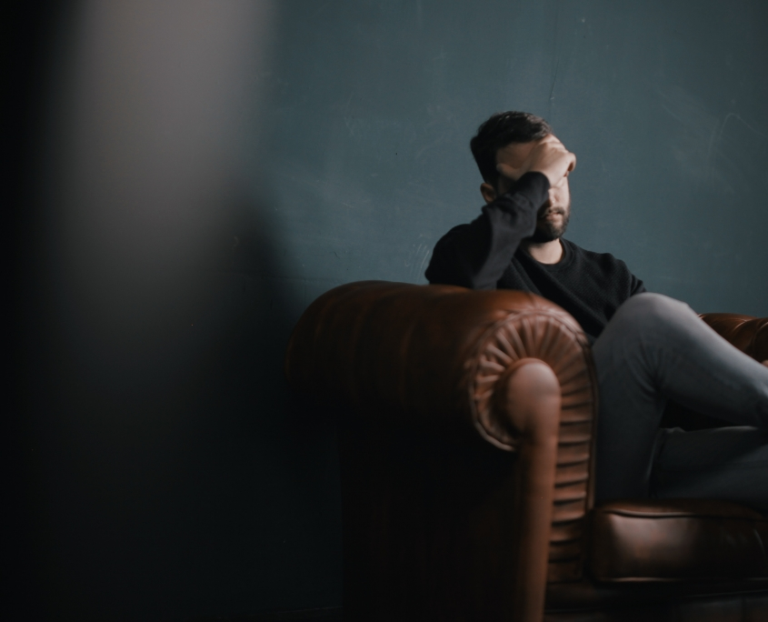 man sitting on sofa against wall
